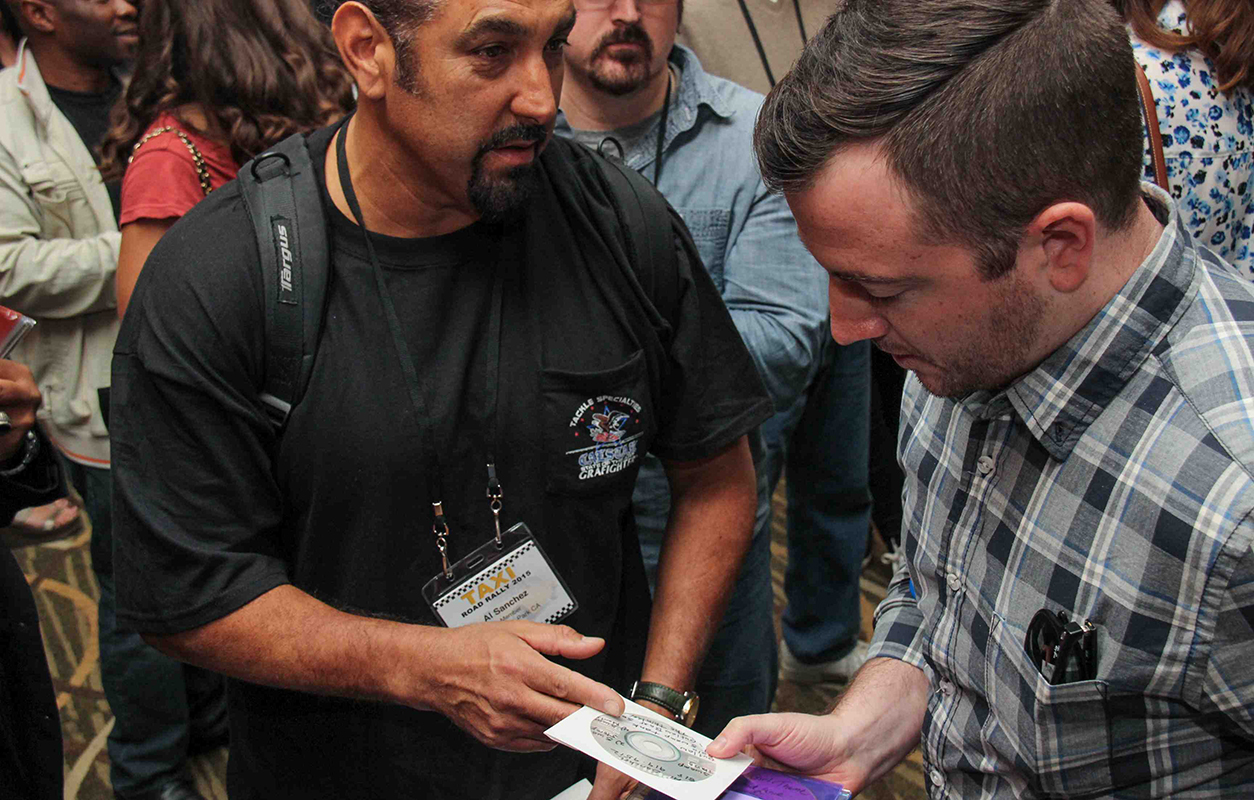 Hollywood Trailer Music Supervisor Naaman Snell takes a look at a CD given to him by TAXI Member Al Sanchez.