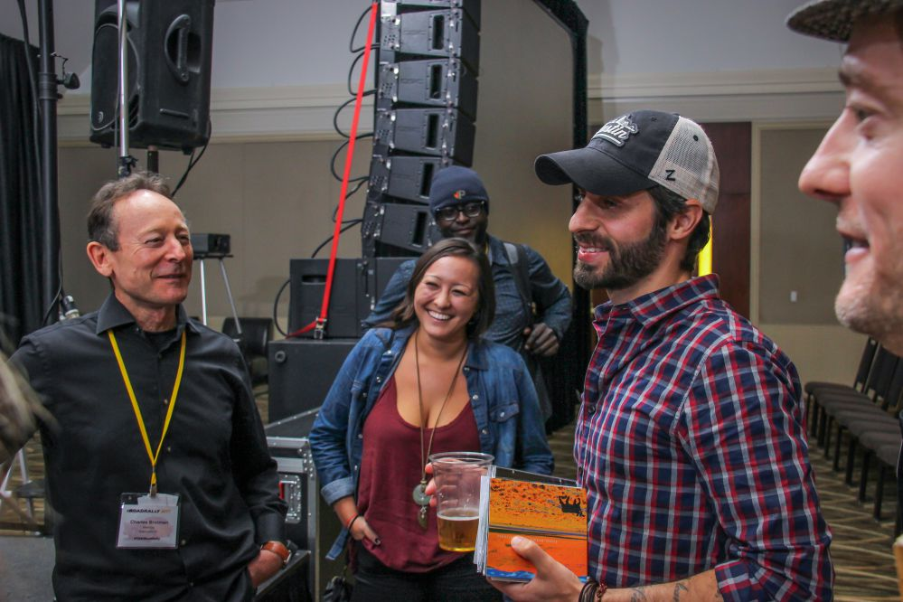 Music Supervisor Frank Palazzolo has a handful of music from TAXI members, a half-full beer, and a big smile on his face when he runs into friends Charles and Julia Brotman after his panel at the Rally.