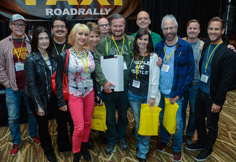 "Matt Hirt (center, green short, big smile) was surrounded by his ""fan club"" of long time TAXI friends after he was honored with the John Braheny Genesis award at the 2018 Road Rally."