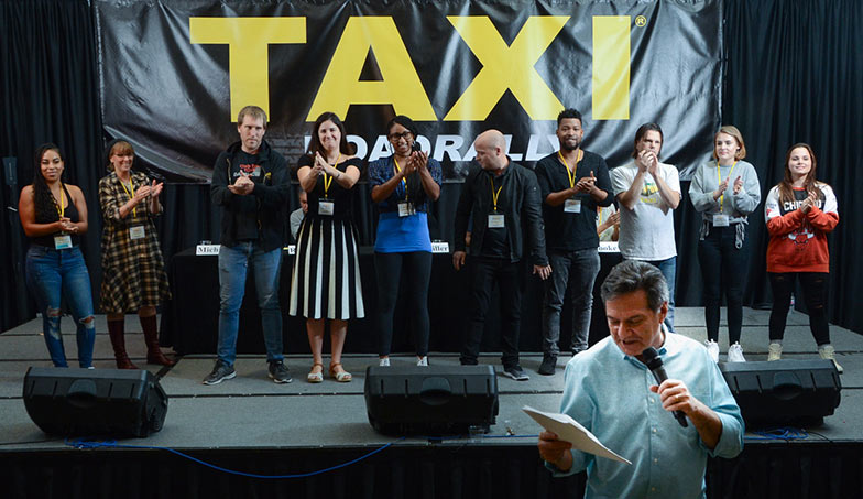 "And the ""boss"" ends the Rally by thanking TAXI's staff for all of their incredibly hard work and long hours that went into making the 2018 Road Rally the best one ever! From left to right, the TAXI staff members are: Angel Maradiaga, Debra Laskow, Matthew Hutchison, Laura Jackman, Enjelique White, Eric Anderson, Isaac Williams, Tom Stillwagon, Briagha McTavish, and Grace Wojick."