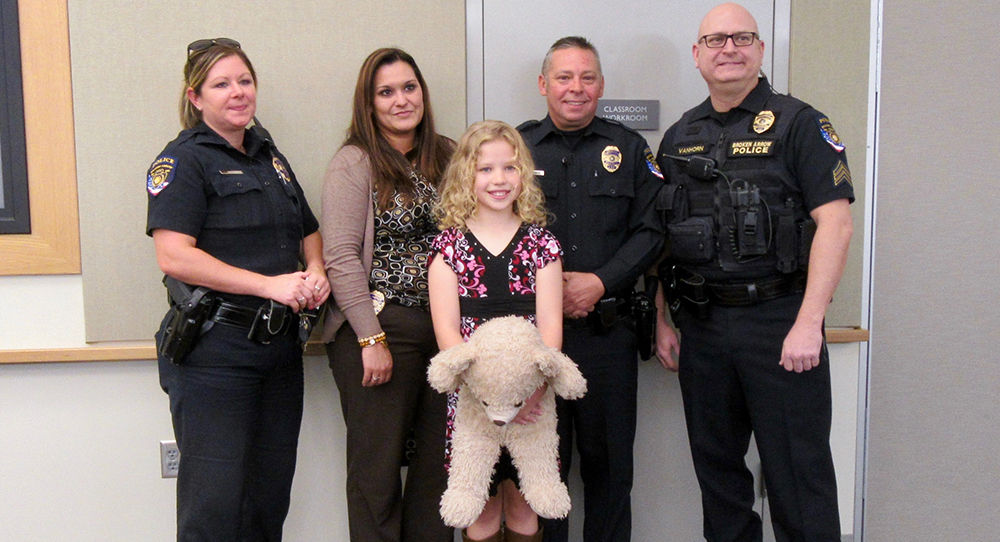 Gwenevere and the police offers who helped save her. This shot was taken in 2015, and Gwenevere brought the bear that one of the officers brought her while she was recovering in the hospital.