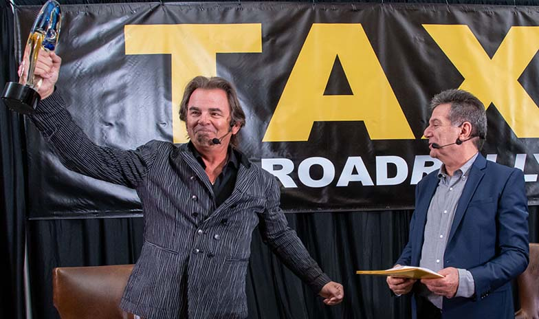Jonathan Cain of Journey, triumphantly holding up his Lifetime Achievement award prior to doing his Keynote Interview with TAXI's Michael Laskow.