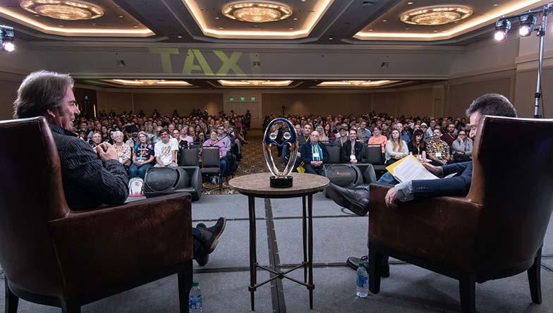 Jonathan Cain (left) seems to be enjoying his Keynote Interview in front of a standing-room-only audience. Cain was TAXI's Lifetime Achievement Award recipient for 2019.