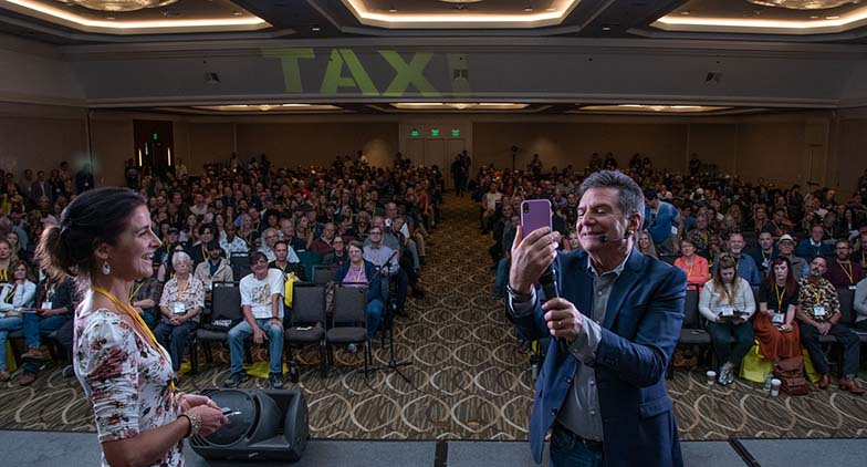 "TAXI member Ragani Buegel let Michael Laskow use her phone to FaceTime with long-time member Matt Hirt, who now lives in Switzerland and couldn't be at the Rally. Matt got to say ""hello"" to his many friends in the audience. It was almost as good as being there, at least for a couple of minutes."