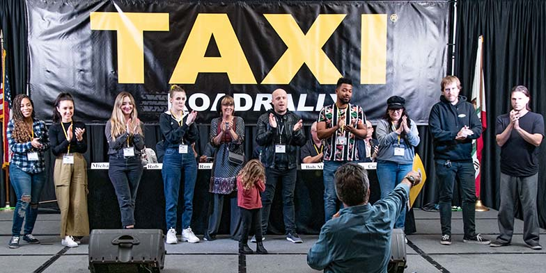 Michael called the staff up to the stage to take a bow and get a well-deserved standing ovation at the end of the Rally. From the left, they are: Angel Maradiaga, Angela Mukul, Ariana Cubillos Voegler, Briagha McTavish, Debra Laskow, Eric Anderson, Isaac Williams, Liz Cohen, Matt Hutchison, and Tom Stillwagon. We have no idea who that kid is, and how she got on stage ;-).