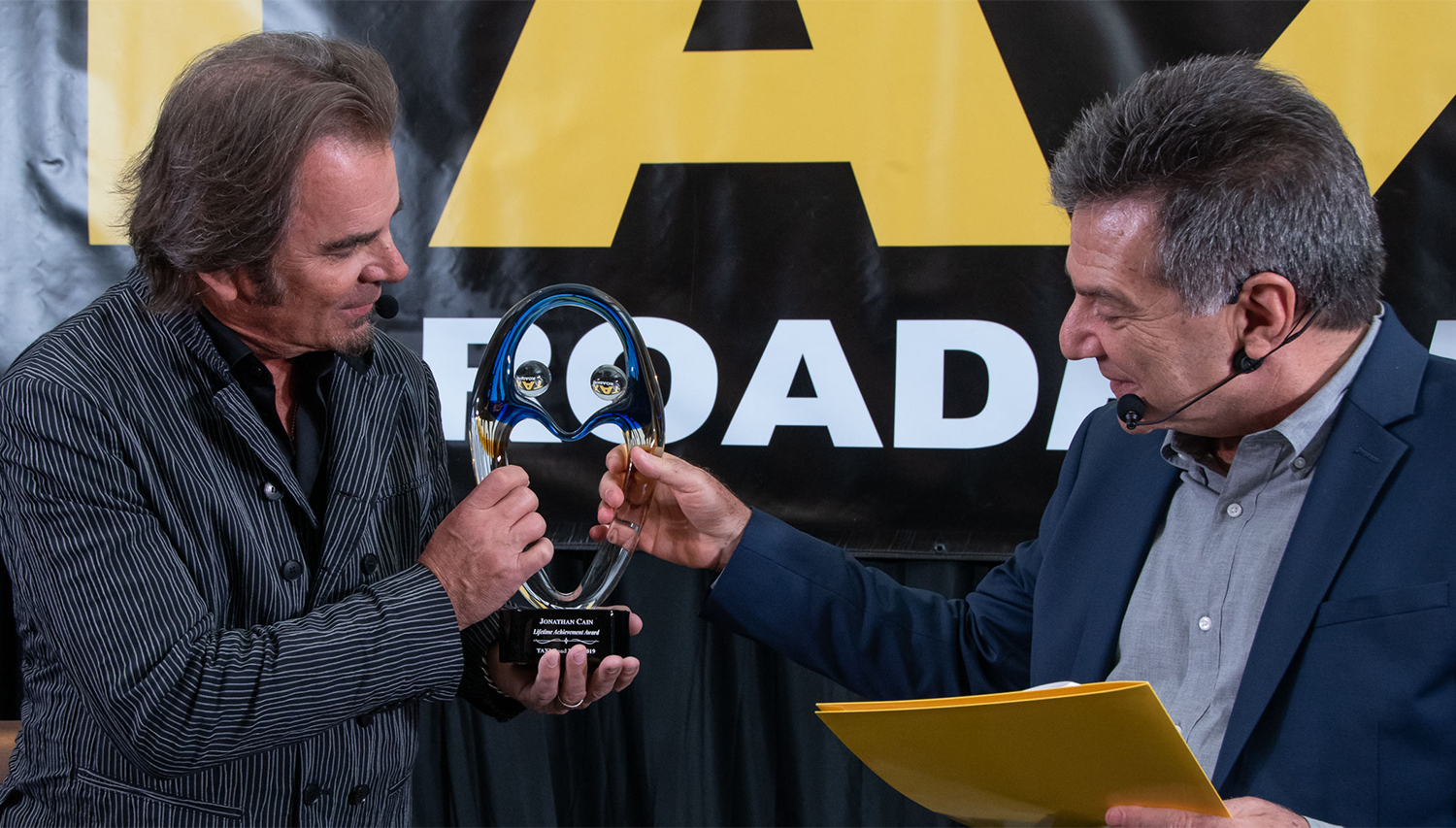 Jonathan Cain proudly holds up his Lifetime Achievement Award at the TAXI's Road Rally, while Michael Laskow congratulates him.